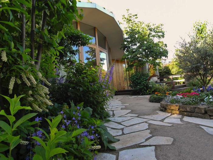 特徴的な建物全面にある窓から庭全体が眺められます。お庭の奥だけでなく、建物際にも植栽を設けています。