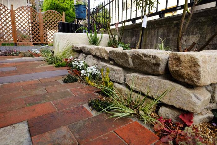 自然石を使った花壇はレンガ敷きとの隙間にも植栽することで、より自然の雰囲気がでてきます。